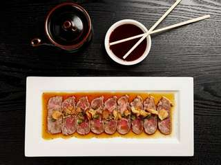 Beef tiradito-style carpaccio is served at Nikkei of