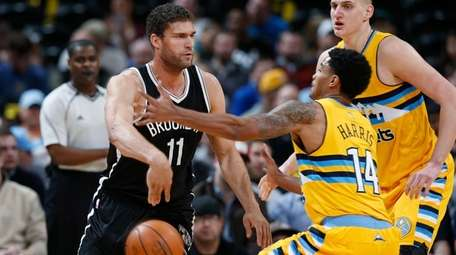 Brooklyn Nets center Brook Lopez, left, passes the