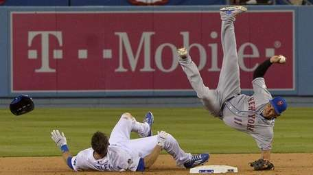 New York Mets shortstop Ruben Tejada falls after