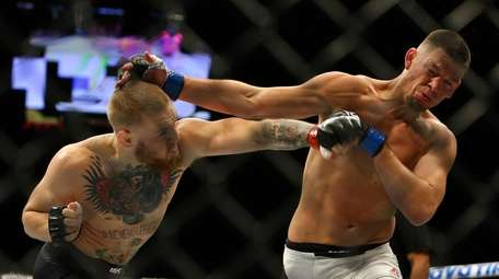 Conor McGregor punches Nate Diaz in a welterweight