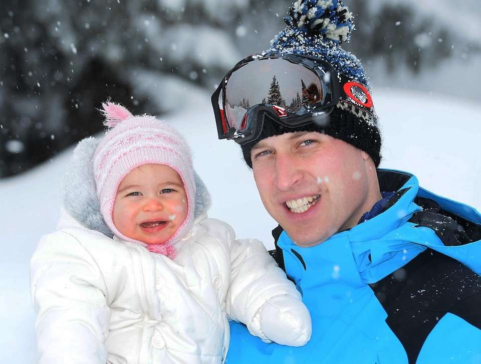 Britain's Prince William poses with Princess Charlotte as