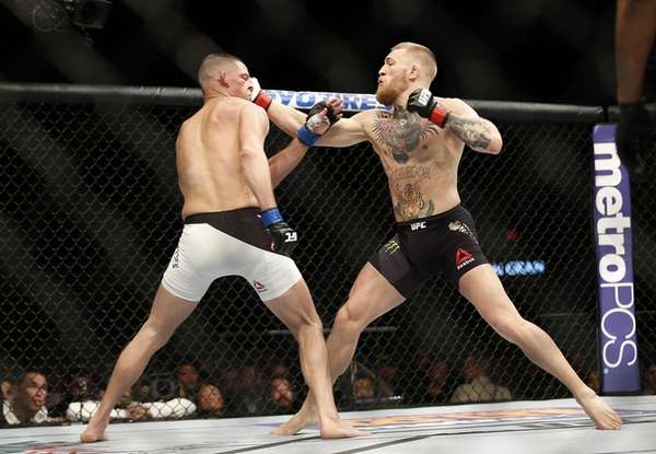 Nate Diaz, left, trades punches with Conor McGregor