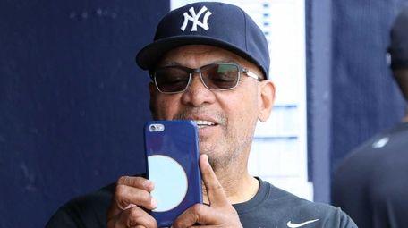 Reggie Jackson takes photos in the dugout during