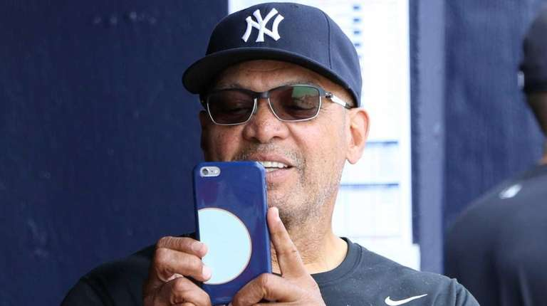 Reggie Jackson takes photos in the dugout during