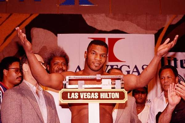 Mike Tyson raises his arms on Friday, Nov.