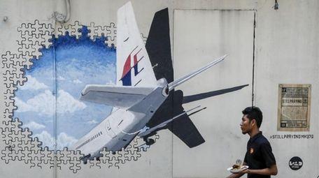 A waiter walks past a mural of Flight