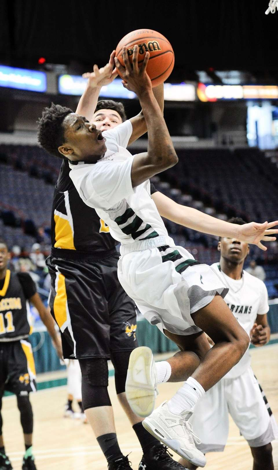 Elmont's Travis Robinson-Morgan ,front, is fouled by High