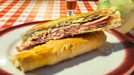 A Cuban sandwich with roasted pork, cooked ham,