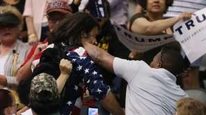 Trump protester Bryan Sanders, center left, is punched