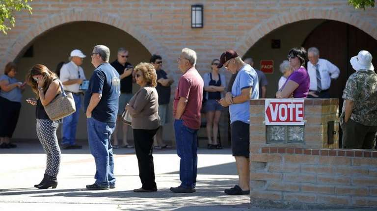 Voters wait in line to cast their ballot