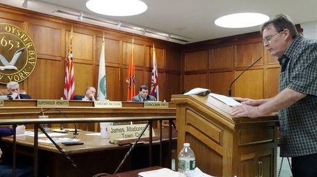 Oyster Bay Town Supervisor John Venditto listens as