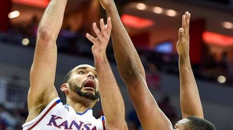 Kansas forward Perry Ellis shoots over Maryland center