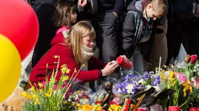 A woman lights a candle at floral tributes