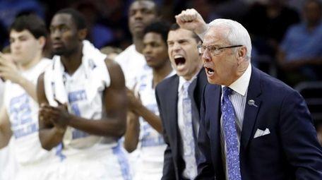 North Carolina coach Roy Williams and players react