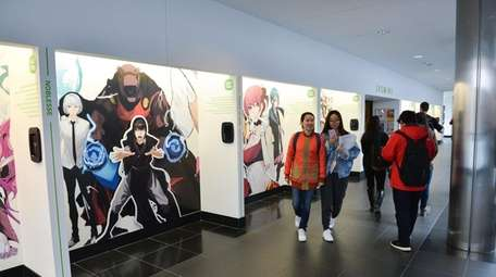 Students pass by a display of webtoon artwork