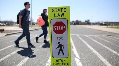 Pedestrians use a crosswalk outside the Suffolk County