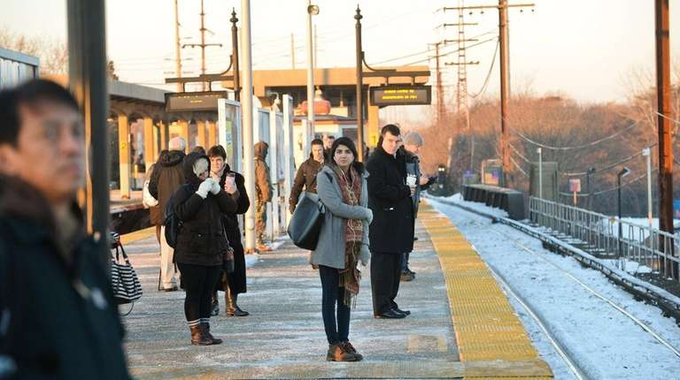 Passengers wait for a delayed Manhattan-bound train at