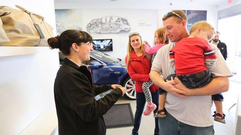 Tesla Product Specialist Hannah Hunter, left, helps Dawn