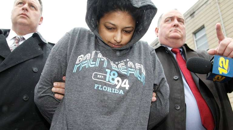 Sharon Seudat is escorted from Nassau County police