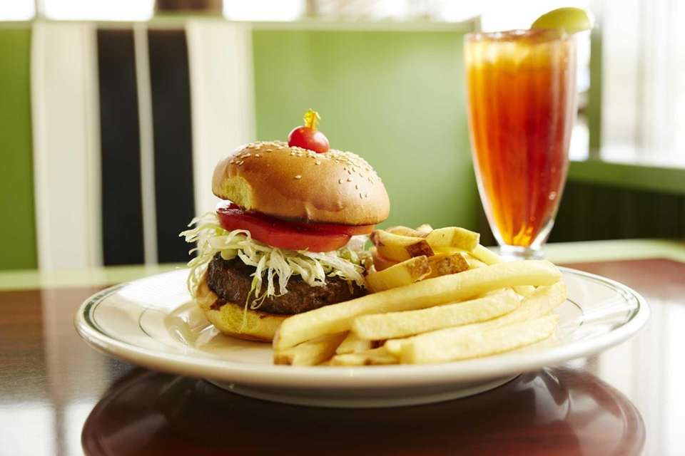 A hamburger with tomato, lettuce and French fries