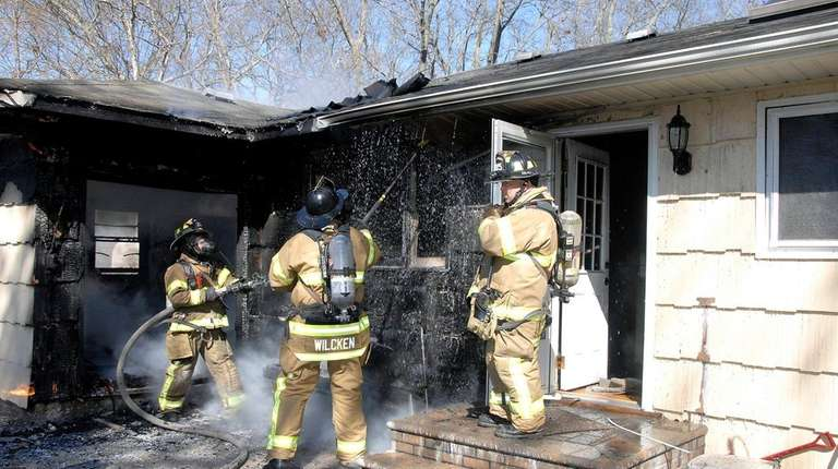 Firefighters spray a Nesconset home with water Sunday,