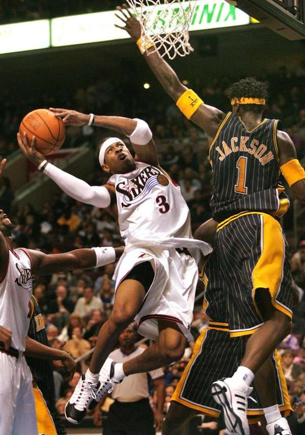 The Philadelphia 76ers' Allen Iverson, left, tries
