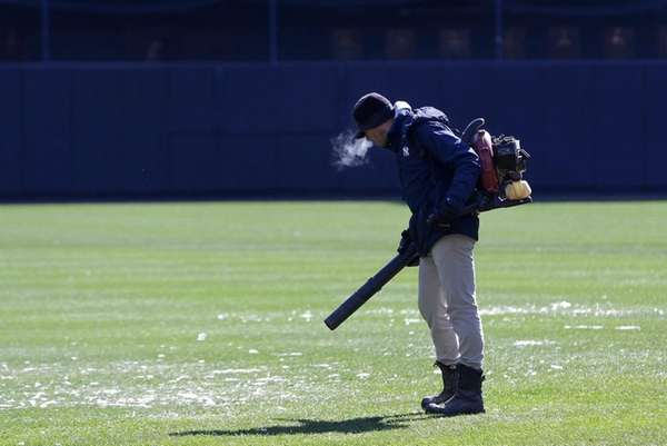 A member of the grounds crew blows