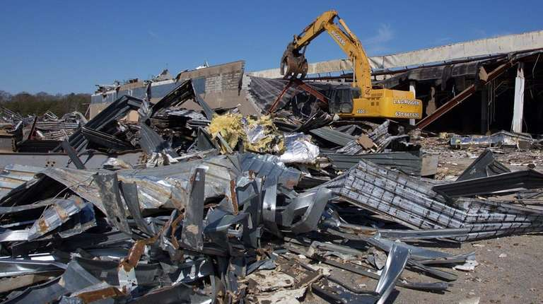 A contractor begins the demolition of the long-vacant