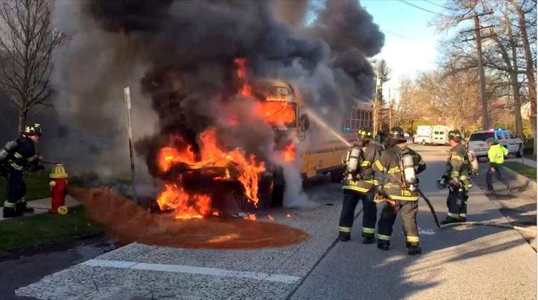 Firefighters hose down flames engulfing a school bus