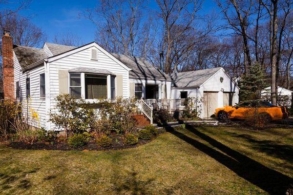 The Port Jefferson house backs a treed property