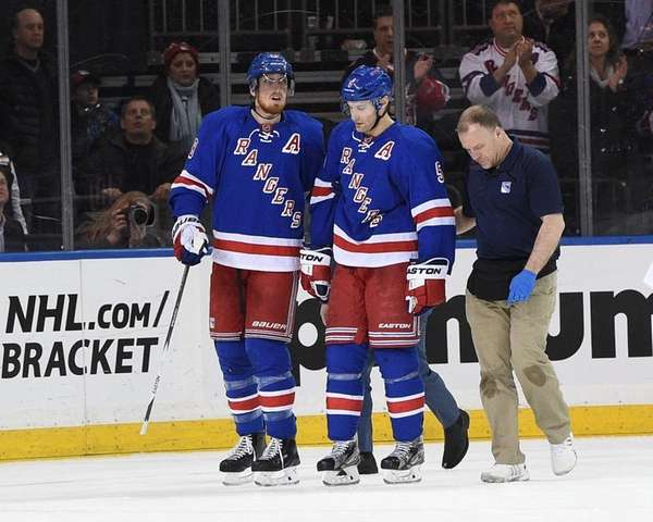 Rangers defenseman Dan Girardi, center, is assisted off