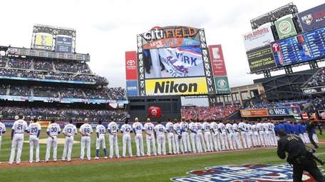 New York Mets players watch as the traditional
