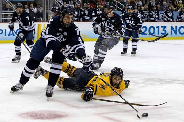 Yale's Rob O'Gara clears the puck after colliding