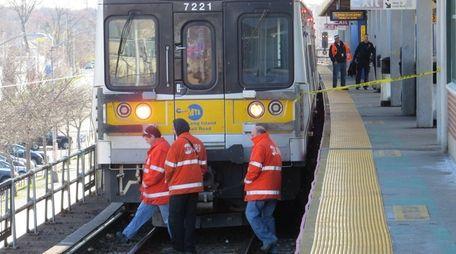 Metropolitan Transportation Authority officials investigate the rails in