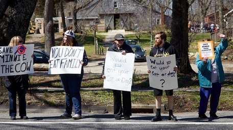 Protesters hold signs outside of Benner's Farm in