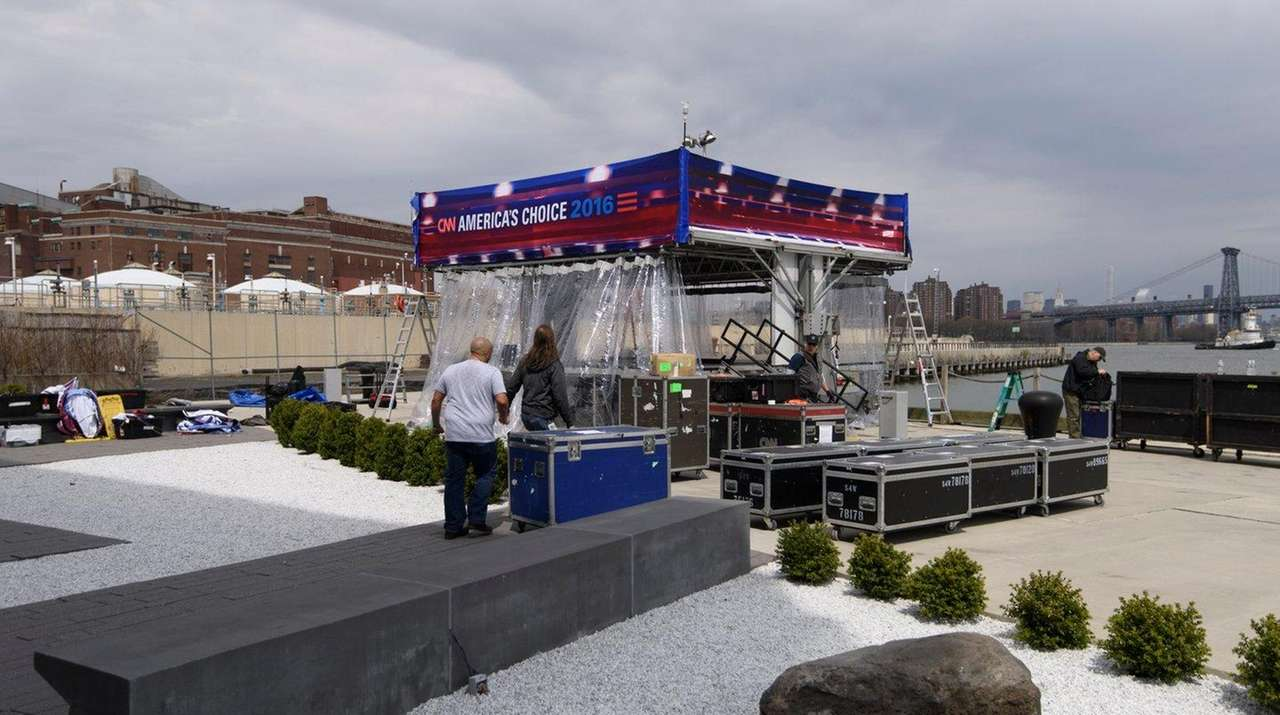 Workers prepare for a debate between Hillary Clinton