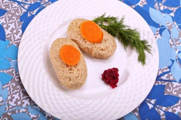 Gefilte fish garnished with carrot, dill and horseradish.