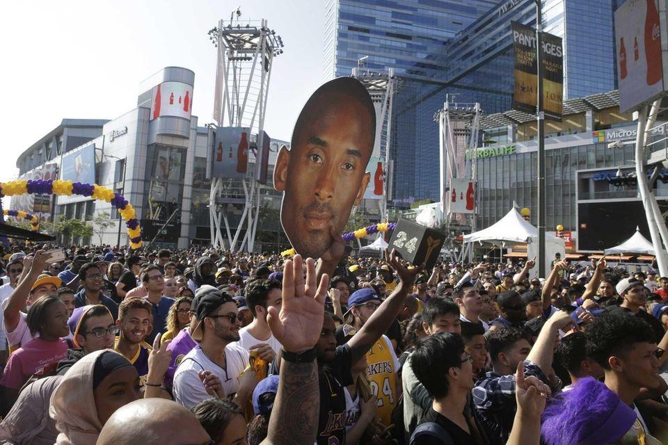 Fans cheer during a fan festival commemorating Kobe