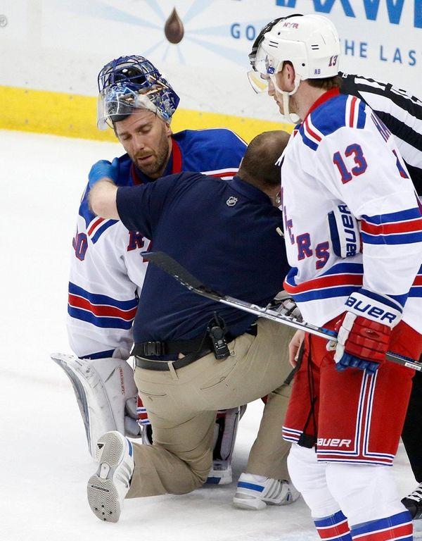 New York Rangers goalie Henrik Lundqvist is helped