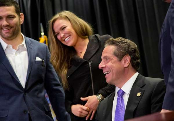 Gov. Andrew Cuomo, right, smiles with UFC athletes