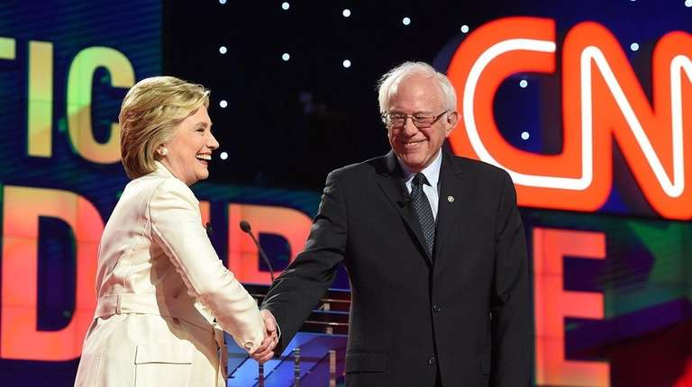 Hillary Clinton and Bernie Sanders shake hands during
