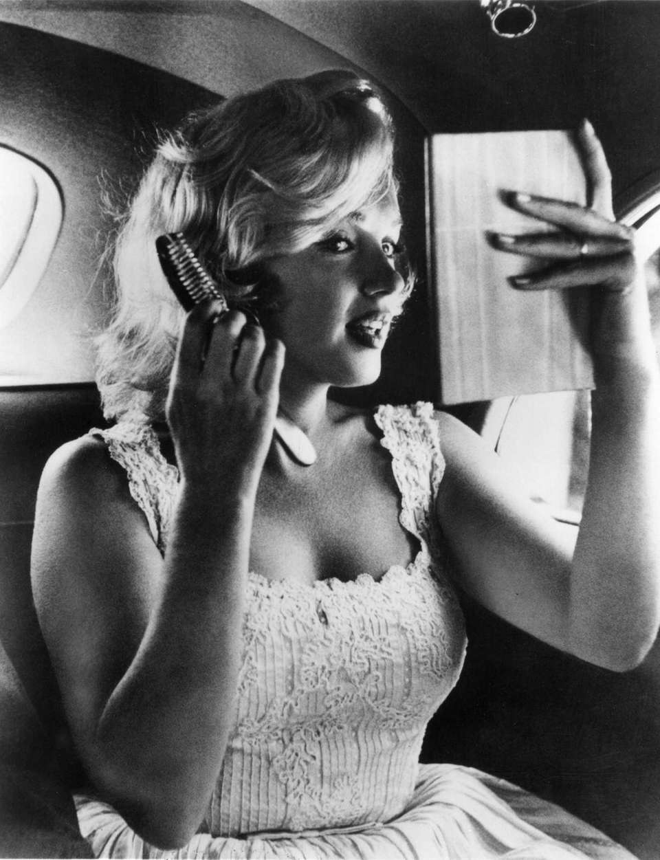 Actress Marilyn Monroe fixes her hair before her