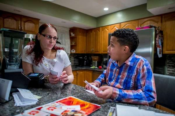 Kristen Franchuk, 31, helps her son, Elijah, 9,