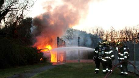 Commack firefighters turn a hose on a burning