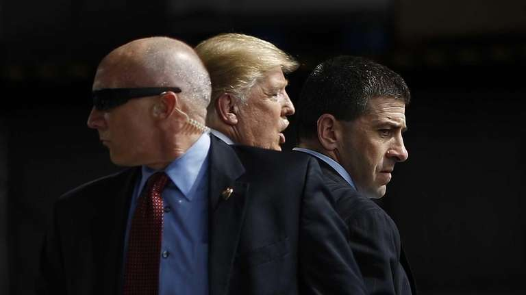 Secret Service agents surround Republican presidential candidate Donald