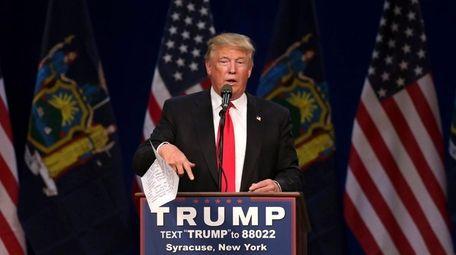 Republican presidential candidate Donald Trump tosses his speech