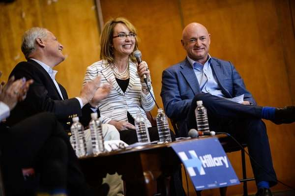 Former Rep. Gabby Giffords, center, speaks while sitting