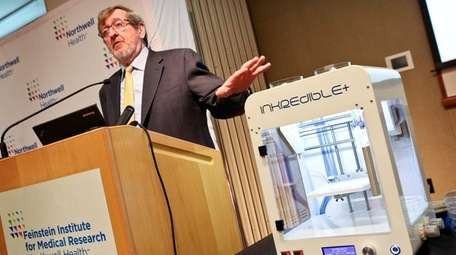 Pointing to a 3D bioprinter, Michael Dowling, president