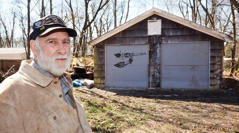 Arthur Schnittger stands near his garage in Islip