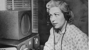 Mrs. Dorothy Strauber of Lynbrook uses earphones to